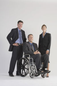 three business people posing for a photo. One person is in a wheelchair.