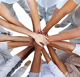 a group of cooworkers put ll their hands into the center as a show of teamwork